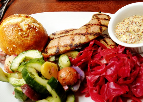 The Marrow - grilled housemade bratwurst with sauerkraut, potato cucumber salad and pretzel roll